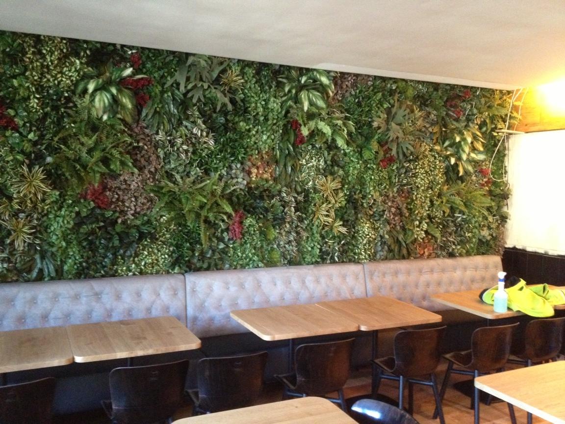 Groenwand met diverse kleurrijke planten bij Restaurant Zoetelief in Den Bosch.