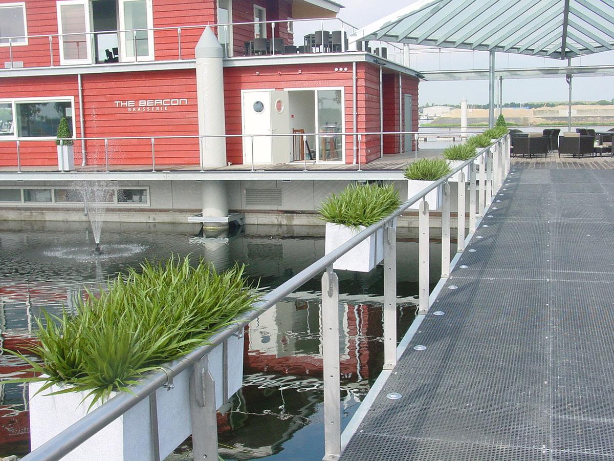 Kunstgrassen in plantenbakken gemonteerd aan een reling. Het hele jaar door mooie groene grassen, uv bestendig.